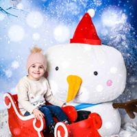 holčička v sáních sedící před sněhulákem